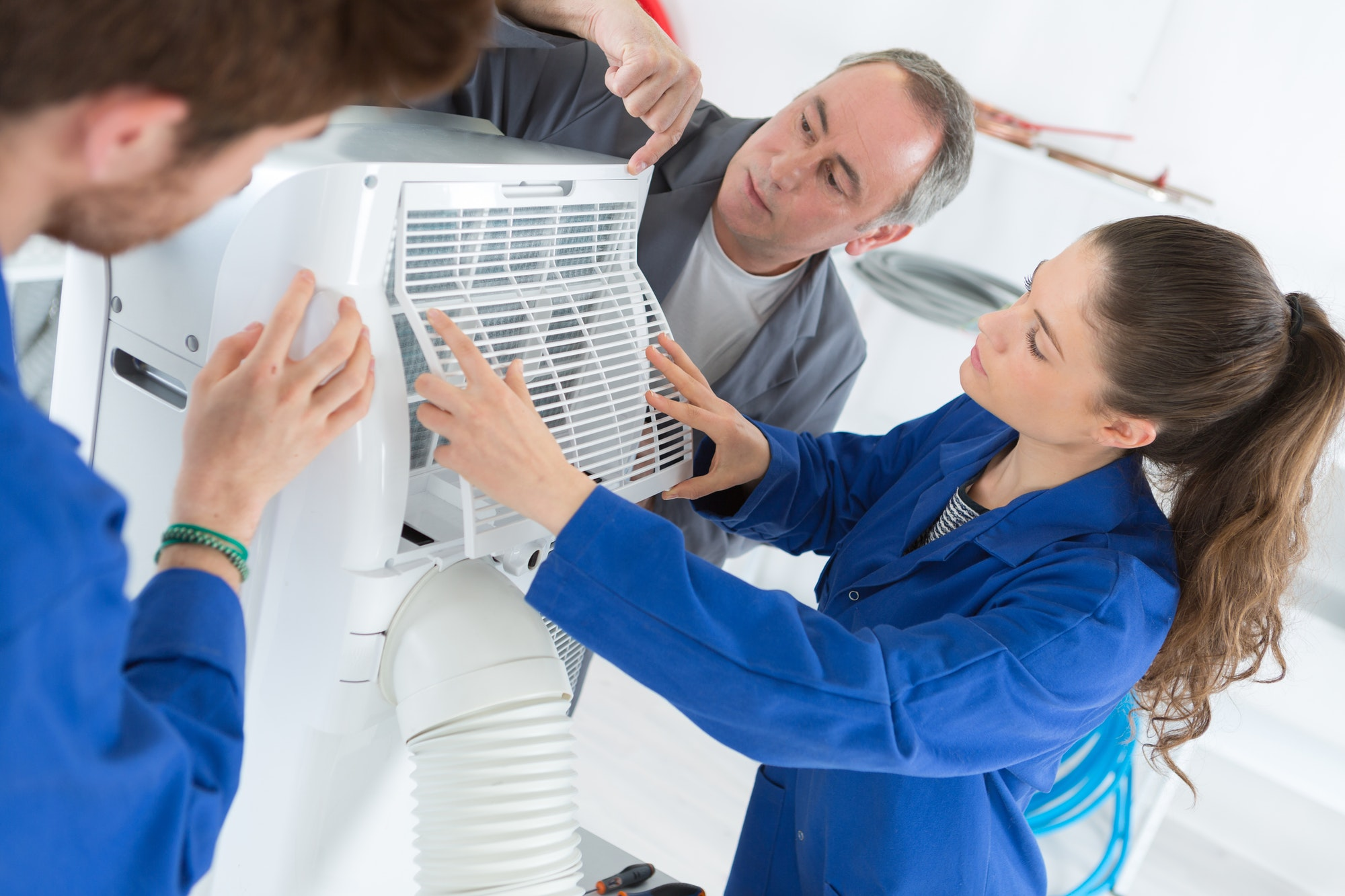 Trainees working on an air conditioning unit
